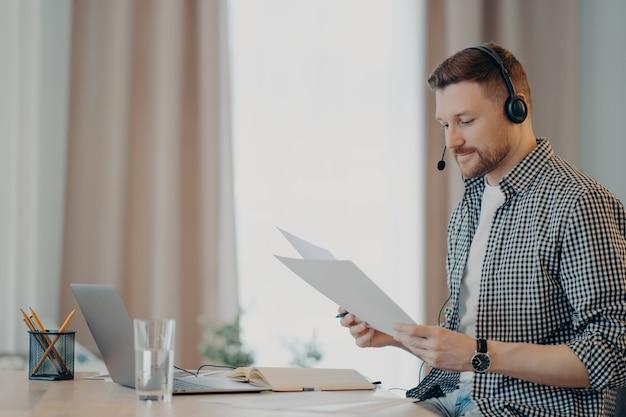 Vista lateral do freelancer jovem sorridente, olhando para documentos e sentindo-se satisfeito enquanto está sentado à mesa e usando o laptop. cara segurando papéis e trabalhando remotamente em casa
