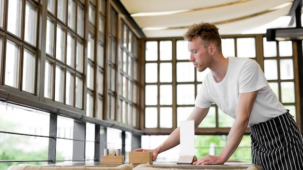 Vista lateral do garçom masculino preparando mesas