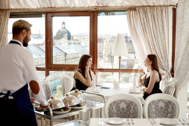 Vista lateral do garçom que está servindo o jantar para duas mulheres bonitas amigas no restaurante elegante com vista perfeita da janela