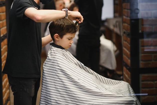 Vista lateral do garotinho fofo cortando cabelo de cabeleireiro na barbearia