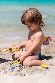 Vista lateral do garoto ajoelhado brincando com areia na praia