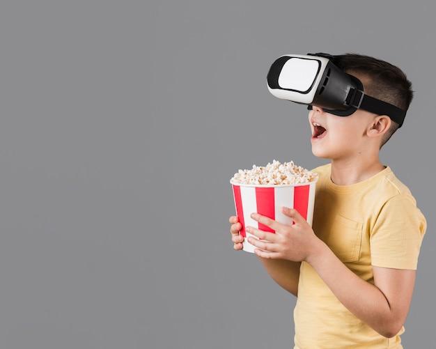 Vista lateral do garoto feliz segurando pipoca e usando fone de ouvido de realidade virtual