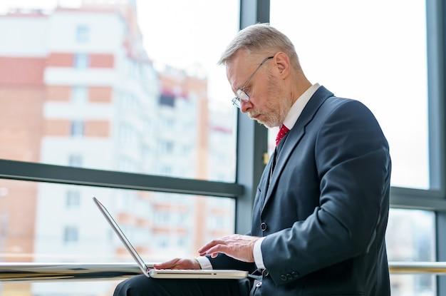 Vista lateral do gerente de trabalho. homem de terno com laptop perto de uma janela grande.