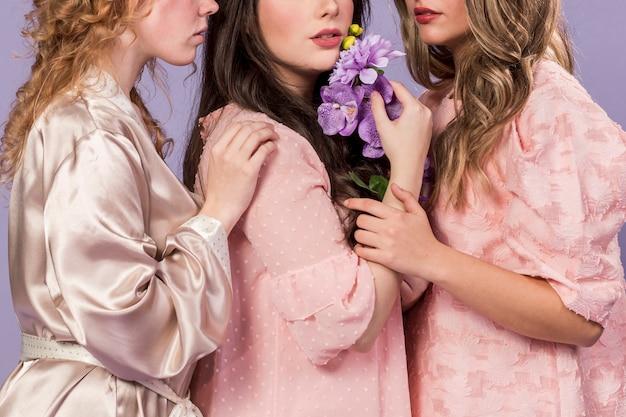 Vista lateral do grupo de mulheres posando com buquê de dálias e orquídeas