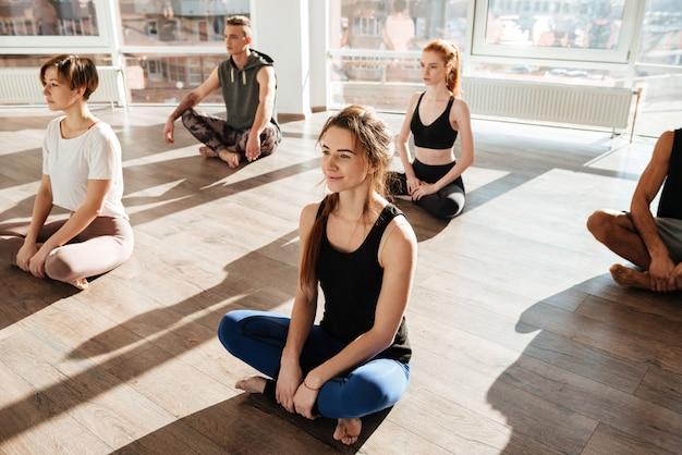 Vista lateral do grupo envolvido ioga no chão