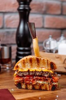 Vista lateral do hambúrguer com anel de cebola na parte superior