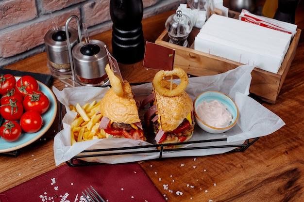 Vista lateral do hambúrguer com batatas fritas e iogurte azedo em cima da mesa