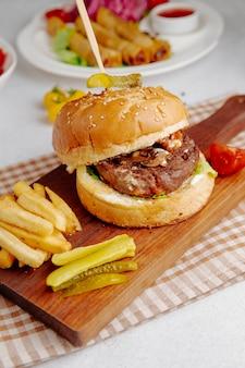 Vista lateral do hambúrguer com batatas fritas em uma placa de madeira