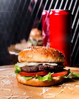 Vista lateral do hambúrguer com carne derretida, queijo e legumes na placa de madeira