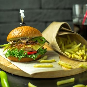 Vista lateral do hambúrguer de frango com queijo derretido tomate e alface, servido com batatas fritas na placa de madeira
