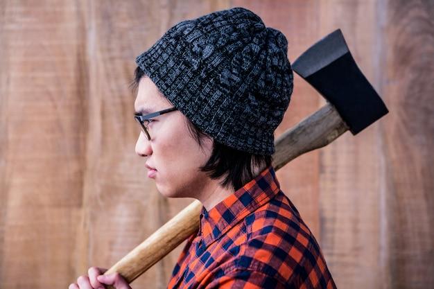Vista lateral do hipster segurando um machado