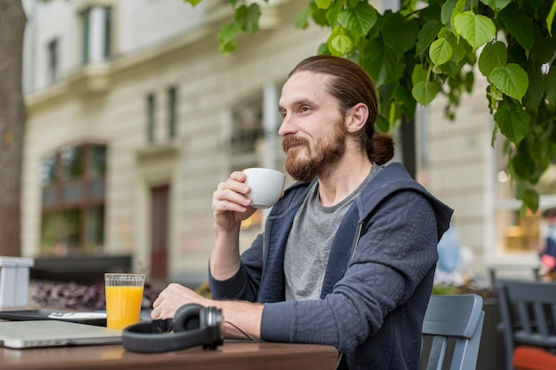 Vista lateral do homem a gostar de café no terraço da cidade