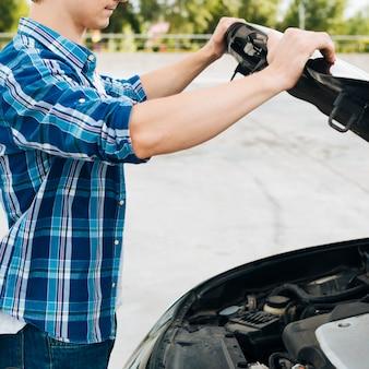 Vista lateral do homem abrindo o capô do carro