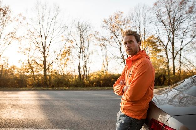 Vista lateral do homem ao lado do carro em uma viagem com espaço de cópia