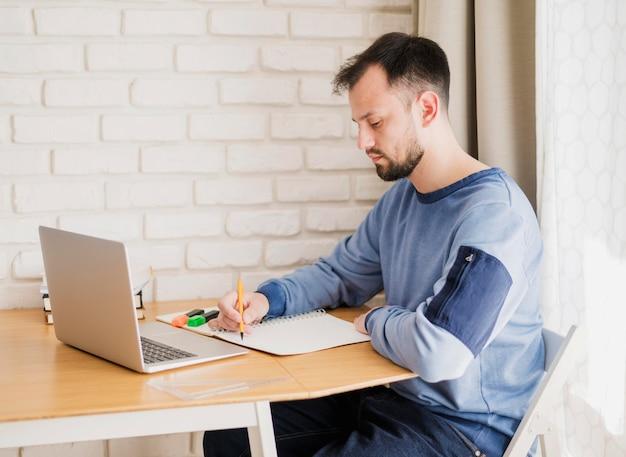 Vista lateral do homem aprendendo on-line do laptop