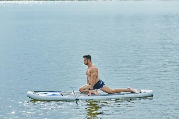 Vista lateral do homem apto a fazer exercícios de alongamento, sentado a bordo do sup.