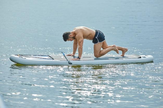 Vista lateral do homem apto a fazer exercícios de fitness, sentado a bordo do sup.
