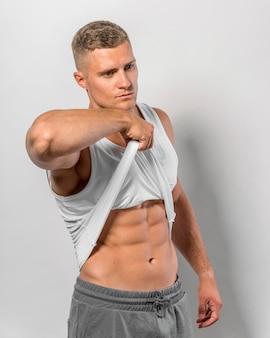 Vista lateral do homem apto mostrando o abdômen através da camiseta
