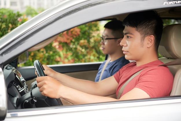 Vista lateral do homem asiático confiante, dirigindo o carro com seu amigo como passageiro