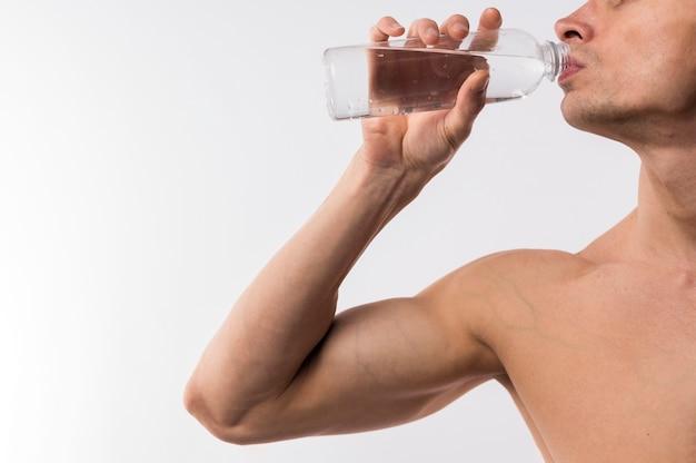 Vista lateral do homem atlético beber água de garrafa com espaço de cópia
