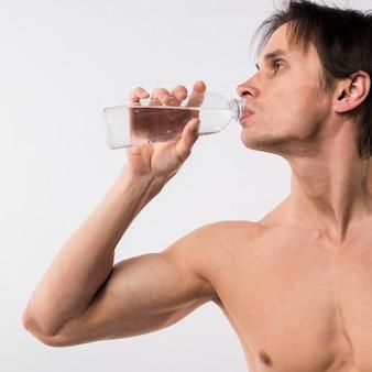 Vista lateral do homem atlético beber água de garrafa