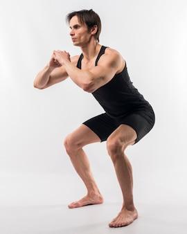 Vista lateral do homem atlético fazendo agachamentos