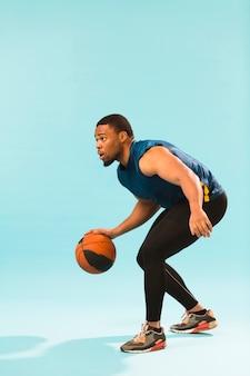 Vista lateral do homem atlético jogando basquete