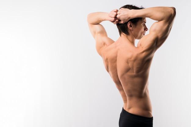 Vista lateral do homem atlético, mostrando o corpo muscular