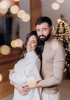 Vista lateral do homem barbudo apaixonado abraça a namorada com um suéter branco no fundo da árvore de natal