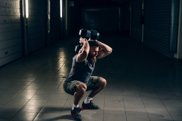 Vista lateral do homem barbudo caucasiano atraente muscular fazendo agachamentos com halteres