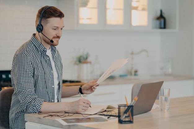 Vista lateral do homem barbudo fazendo anotações no caderno e segurando papéis com dados de negócios enquanto usa o fone de ouvido durante uma chamada online no laptop, sentado em seu aconchegante local de trabalho na cozinha. trabalho remoto em casa