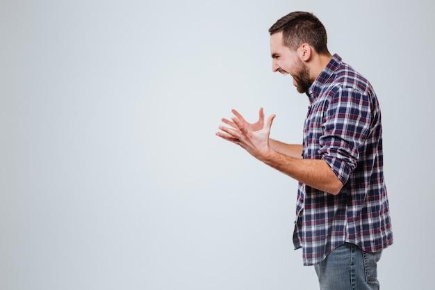 Vista lateral do homem barbudo gritando de camisa