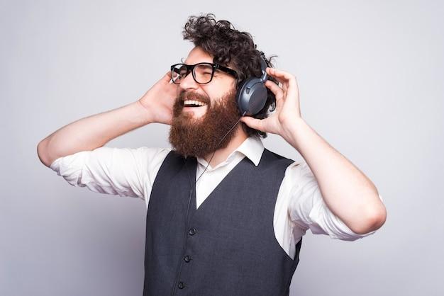 Vista lateral do homem barbudo hipster em terno lietening música em fones de ouvido.