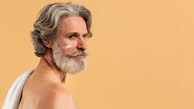 Vista lateral do homem barbudo mais velho com creme no rosto