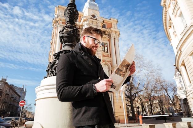 Vista lateral do homem barbudo no casaco com jornal