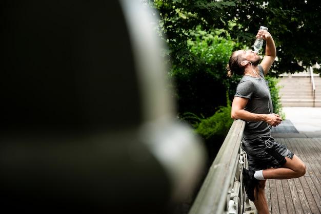 Vista lateral do homem bebendo água no parque
