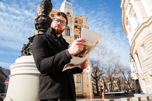 Vista lateral do homem bonito casaco com jornal