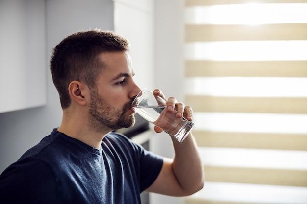 Vista lateral do homem bonito com sede, bebendo água doce. interior da casa.