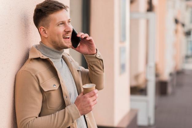 Vista lateral do homem bonito, falando ao telefone