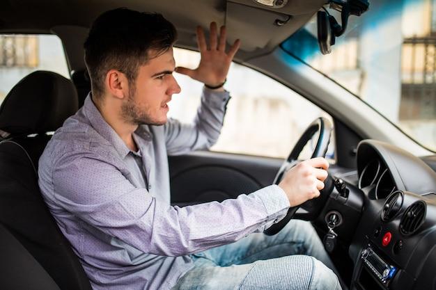 Vista lateral do homem bravo em desgaste ocasional, dirigindo o carro