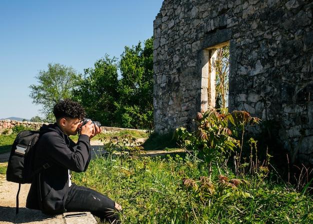 Vista lateral do homem carregando mochila tirando foto da natureza