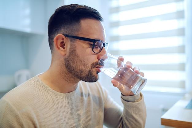 Vista lateral do homem caucasiano bonito sentado na mesa de jantar e água potável.
