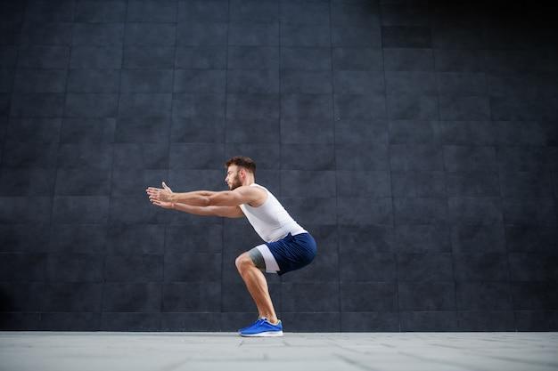 Vista lateral do homem caucasiano musculoso bonito de bermuda e camiseta fazendo agachamento exercício ao ar livre. no fundo é parede cinza.