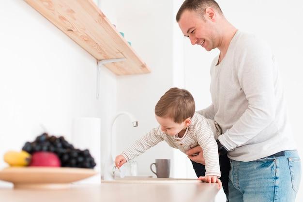 Vista lateral do homem com a criança na cozinha