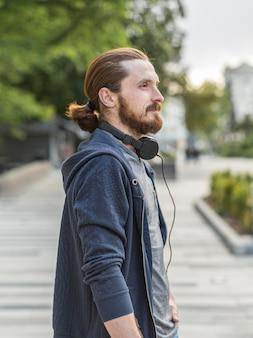 Vista lateral do homem com fones de ouvido na cidade