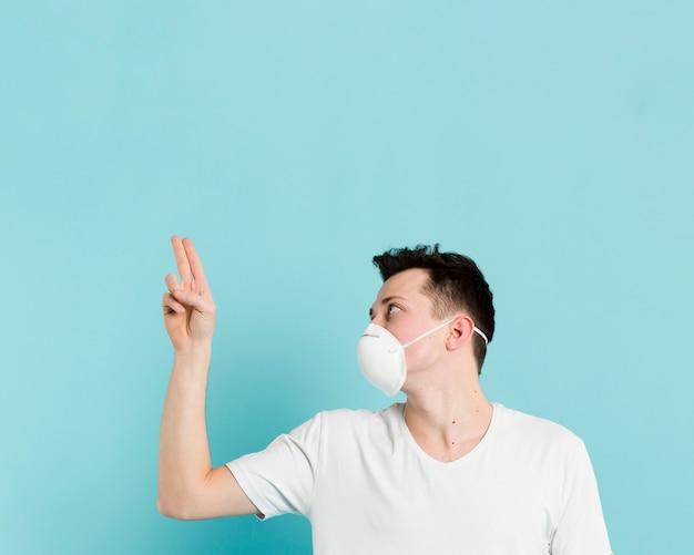 Vista lateral do homem com máscara médica e apontando dois dedos