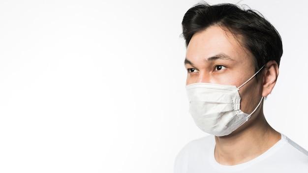 Vista lateral do homem com máscara médica e cópia espaço