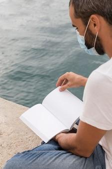 Vista lateral do homem com máscara médica lendo livro à beira do lago