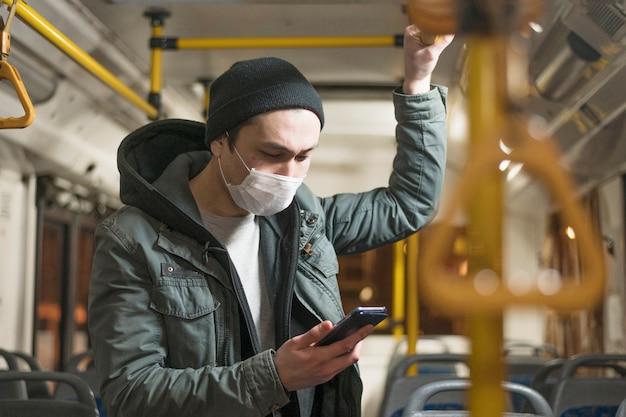 Vista lateral do homem com máscara médica, olhando para o celular no ônibus