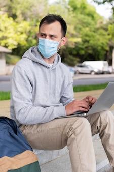 Vista lateral do homem com máscara médica trabalhando no laptop ao ar livre